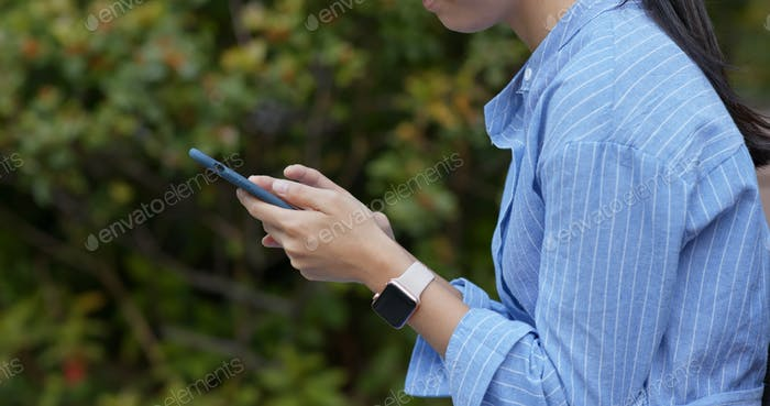 Close up of woman use of mobile phone in the park