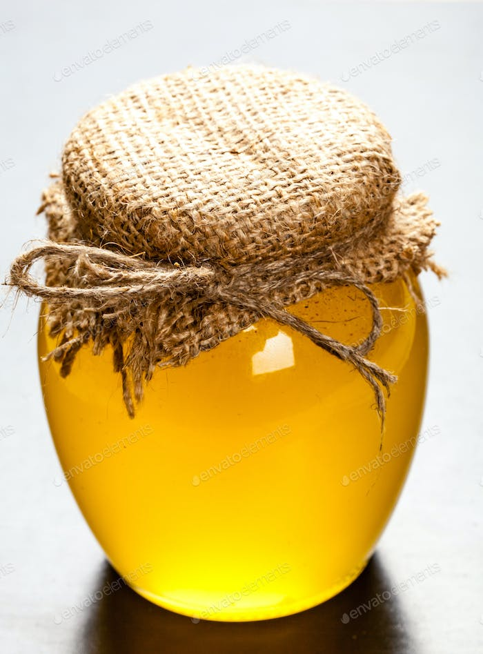 Glass jar with honey isolated on black background