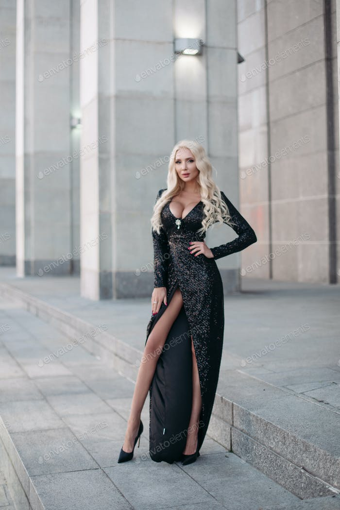Stunning blonde woman in evening gown outdoors
