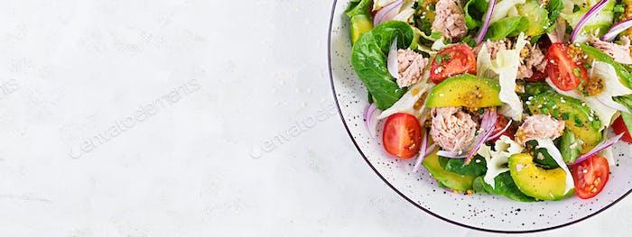 una Fischsalat mit Salat, Kirschtomaten, Avocado und roten Zwiebeln.
