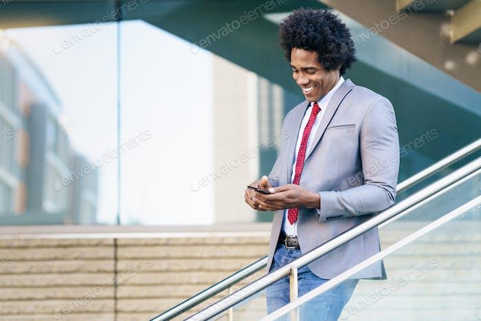 Schwarzer Geschäftsmann mit einem Smartphone in der Nähe eines Bürogebäudes