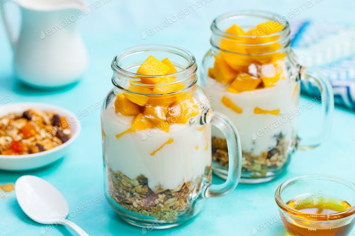 Fresh Mango Fruit with Yogurt and Granola in Jars. Blue Stone Background. Close up.