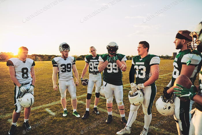 American football players standing on a sports field talking together