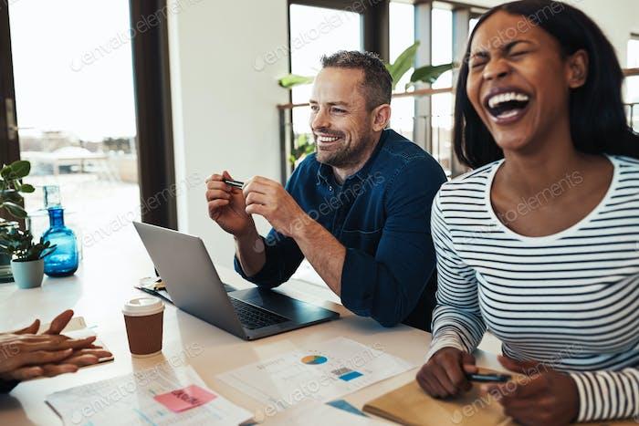 Афро-американская бизнесвумен смеется во время встречи с коллегами по офису