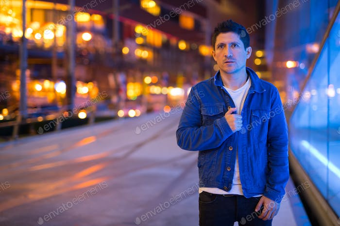 Hispanic man exploring the city streets at night