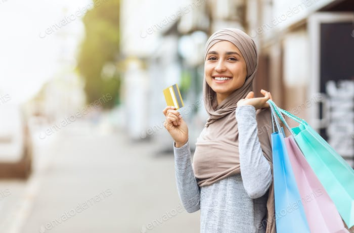 Excited muslim girl with shopping bags showing credit card