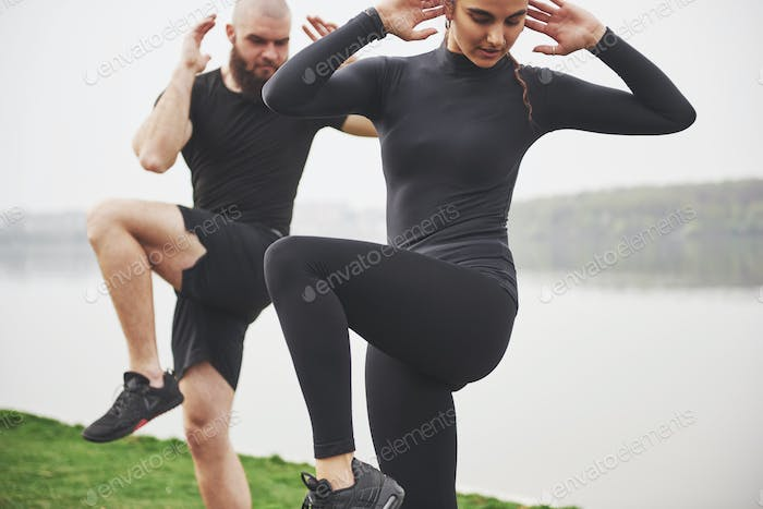 A young couple enjoys playing sports in the morning in the open air. Warm up before exercise