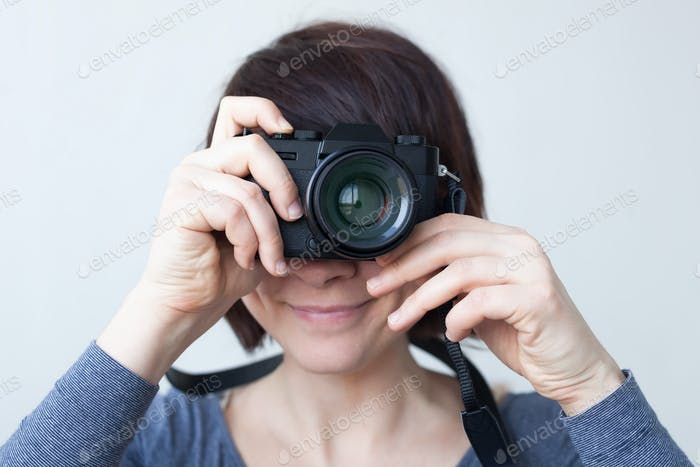 A girl is holding a camera by her face.