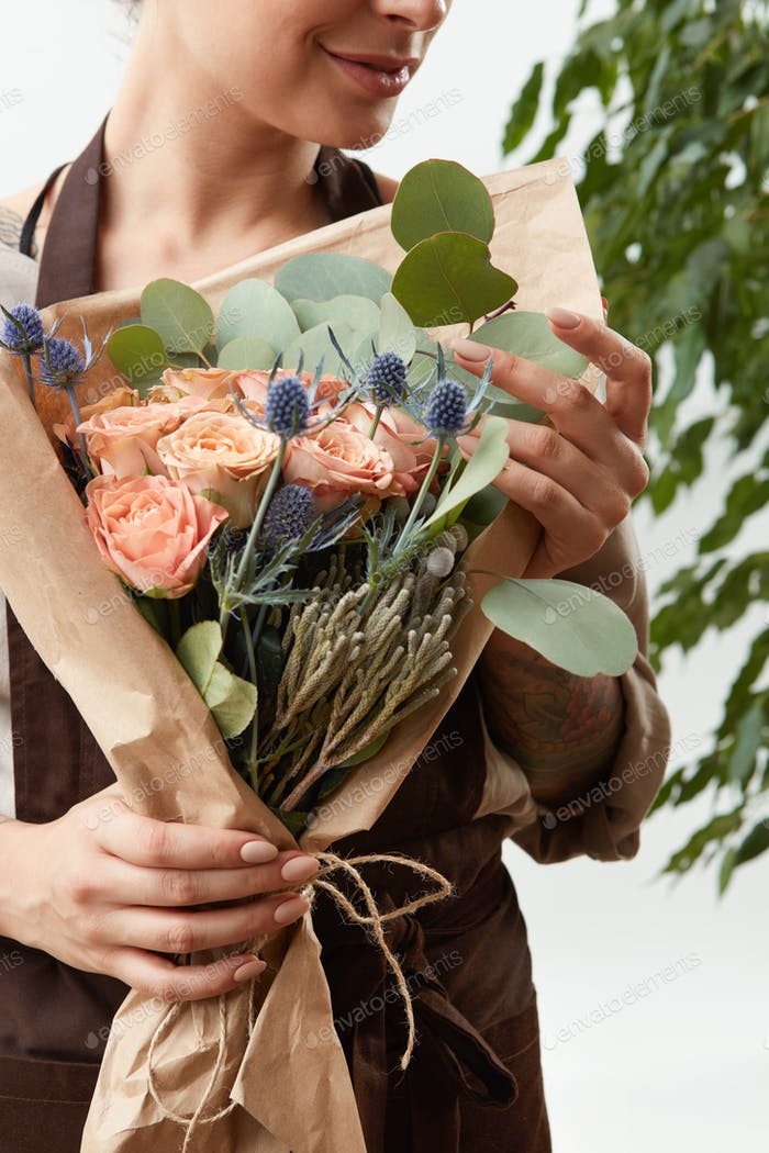 Close-up of greeting flowers bouquet of fresh natural roses living coral color in a florist girl&#39