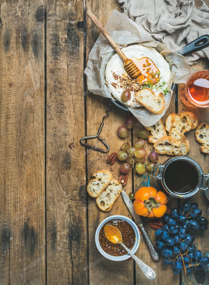 Camembert cheese, fruits, bread, honey, jam and wine, copy space