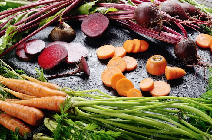 Vegetable background of beets and carrots on kitchen table close