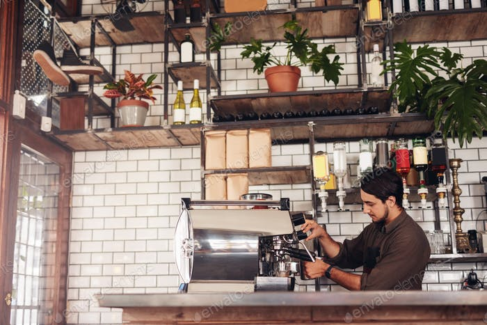 Male barista making a cup of coffee