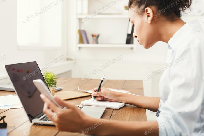 Young woman using laptop with blank screen and making notes
