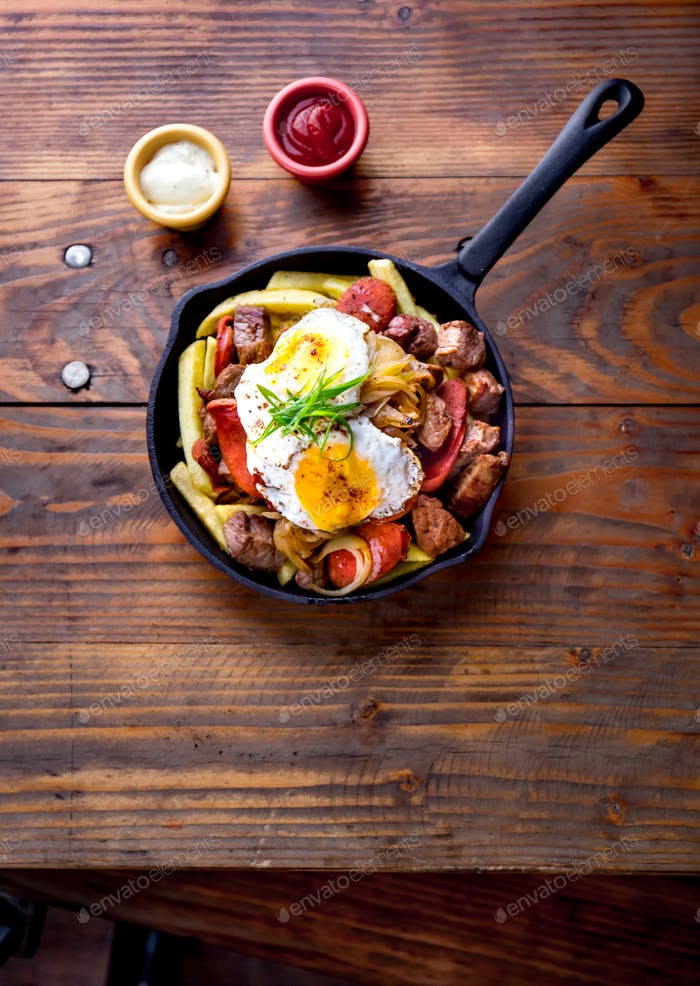 Chilean chorillana french fries topped with beef sliced, chorrisos, fried onion and eggs