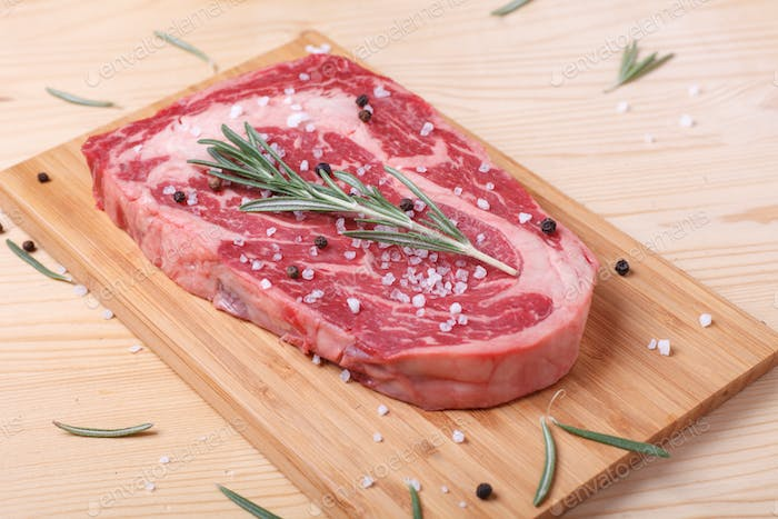 raw uncooked marble beef steak ribeye with spices