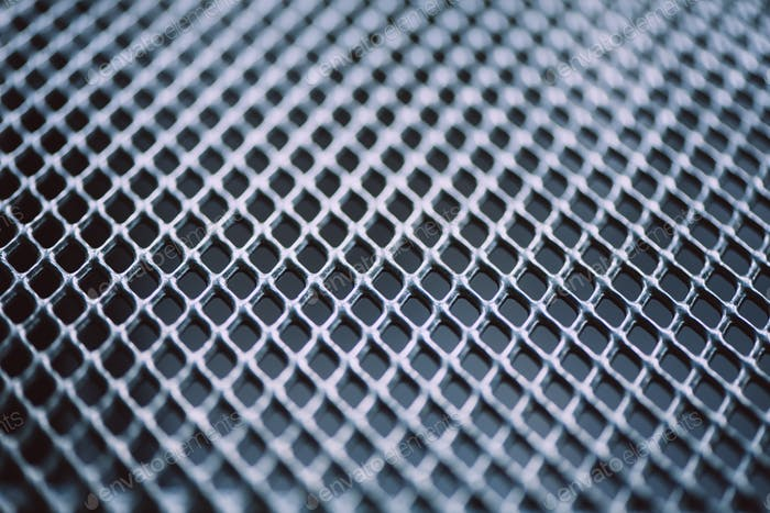 Surface of latticed metal fence. Stainless steel and aluminum light blur background. Macro texture