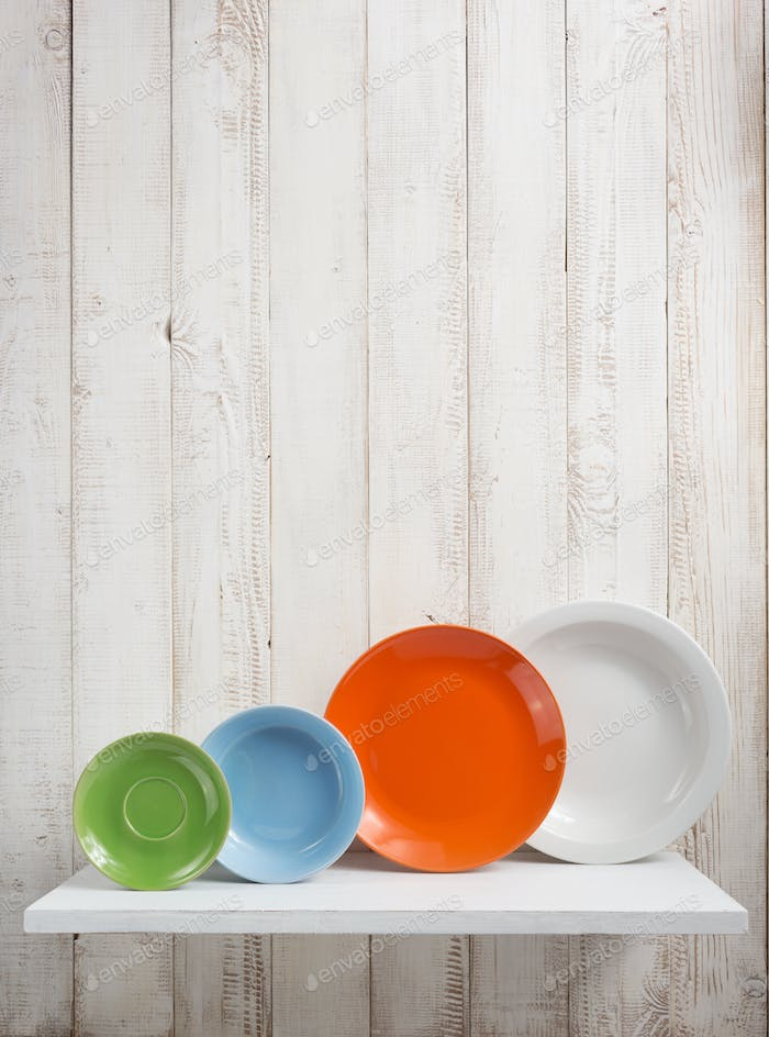 plate at kitchen shelf on wooden background