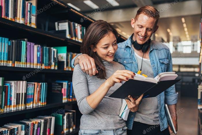 Pareja de jóvenes estudiantes en Biblioteca pública