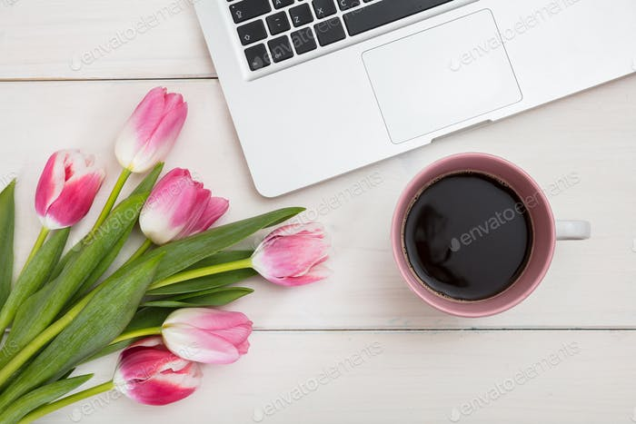 Women's day. Pink tulips, laptop and a cup of coffee on an white