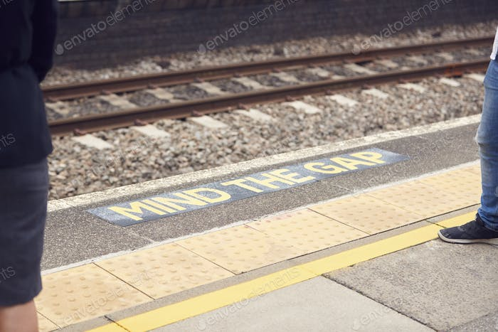 Close Up Of Mind The Gap Sign On Railway Platform With Passengers Waiting For Train