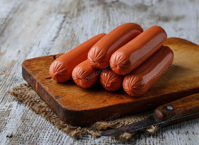 Uncooked sausages on wooden background