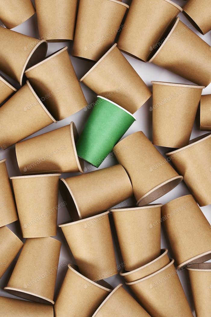 Green disposable mug among  paper mugs