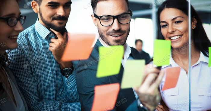 Businesswoman using sticky notes at office to plan project