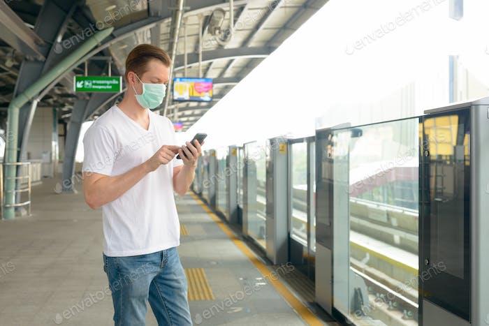Junger Mann mit Telefon mit Maske am Bahnhof