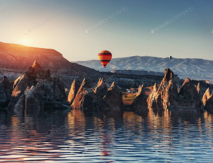 Composition of balloons over water and valleys, gorges, hills, b