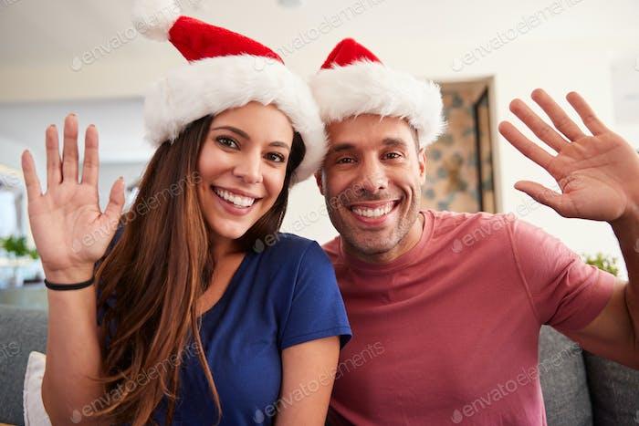 Porträt von Hispanic Paar Tragen Santa Hüte Feiern Weihnachten Winken An der Kamera