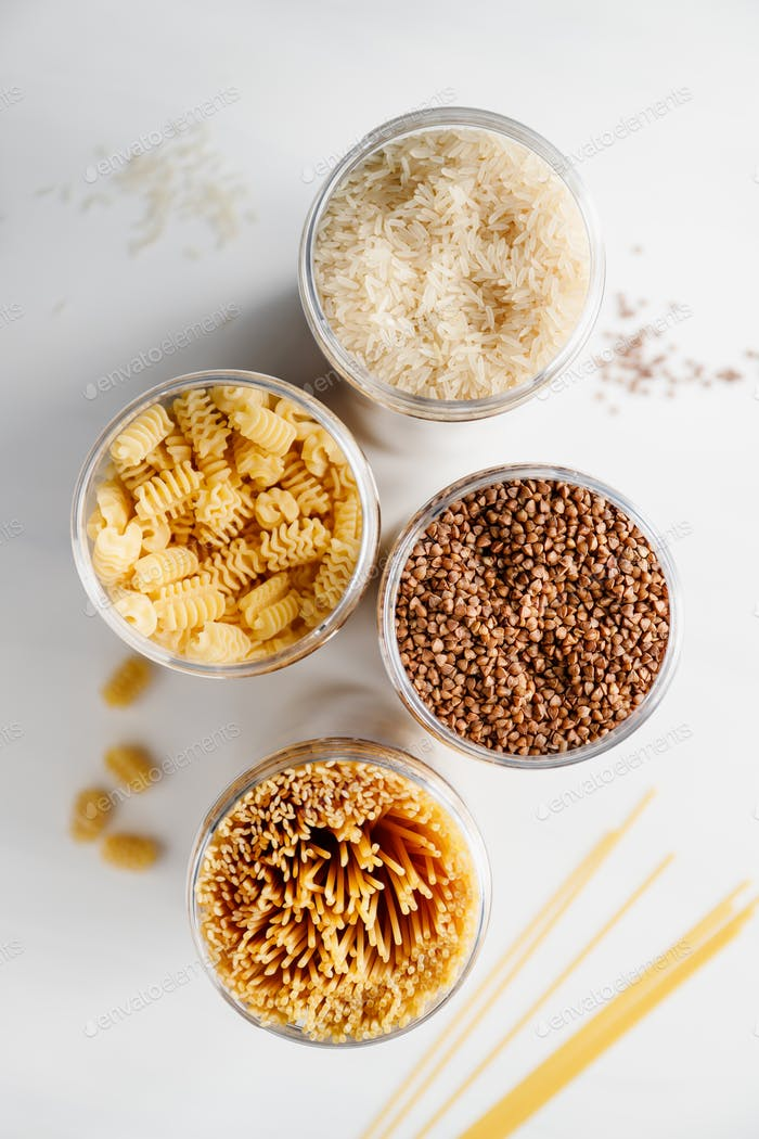 Various pasta and cereal grains in a plastic jars for a long storage.