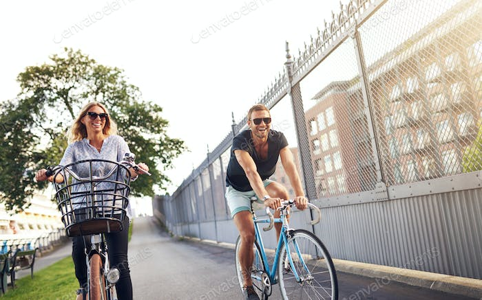 Young couple cycling in an urban park