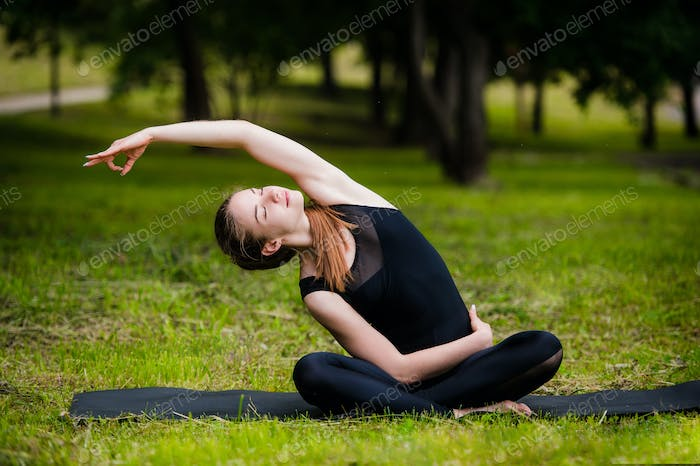 Beautiful young woman doing stretching exercise on green grass at park. Yoga workout