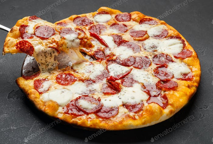 Hot pepperoni pizza with melting cheese on table