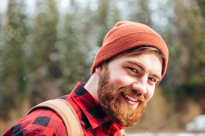 Happy man with beard in hat and checkered shirt outdoors
