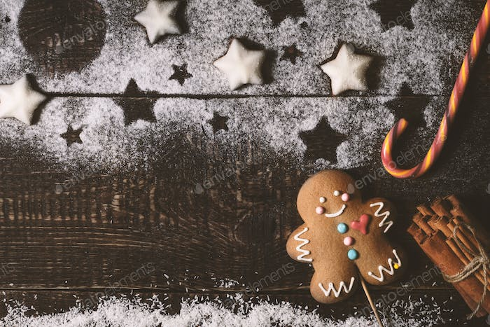Christmas composition with gingerbread man on the wooden table top view