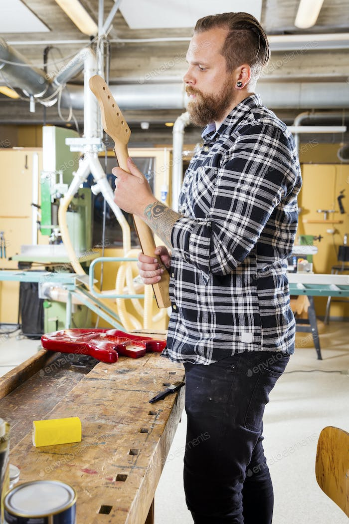 Carpenter inspects a wooden guitar neck in workshop