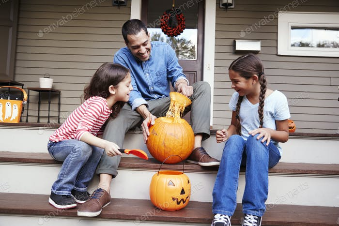 Father And Daughters Carving Halloween Pumpkin On House Steps