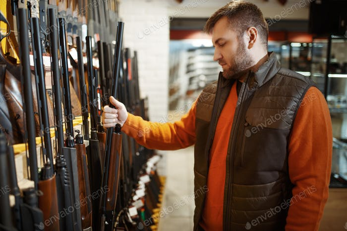 Man choosing rifle at showcase in gun shop