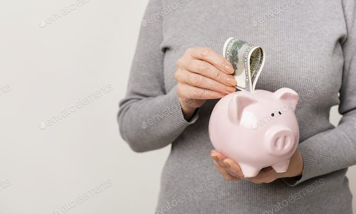 Mujer irreconocible poniendo dinero en la hucha