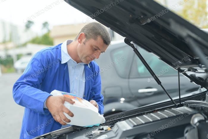 Man refilling vehicle with screen wash