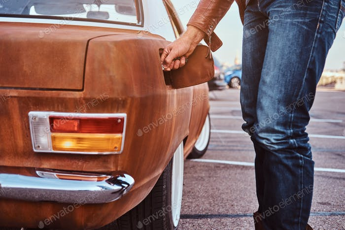 Male hand opens the gas cap of a tuned retro car for refueling.