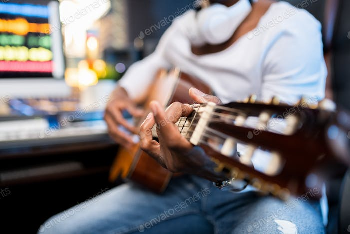 Hands of young musician of African ethnicity on strings of acoustic guitar