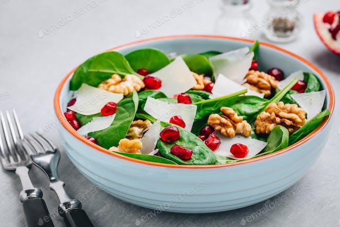 Spinat-Salatschüssel mit Granatapfelkernen, Walnüssen und Käse.