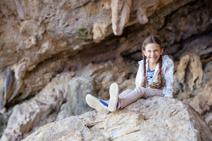 Young girl sitting on rock in climbing sector and smiling