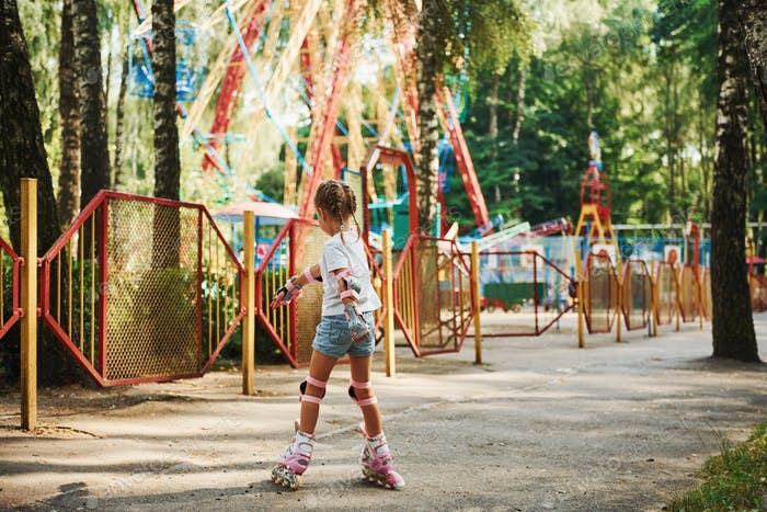 Rear view. Cheerful little girl on roller skates have a good time in the park near attractions