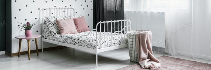 Bright teenage girl bedroom interior with dotted sheets and pink