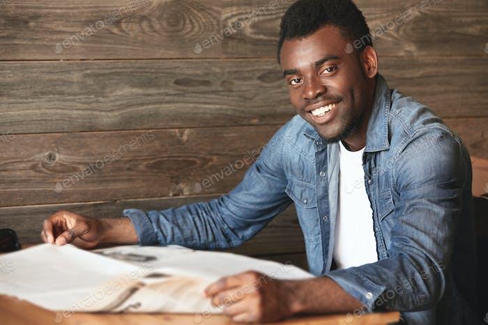 Junger afroamerikanischer Mann sitzt in gemütlichem Café und liest Morgenzeitung. Dunkelhäutiger Youngster