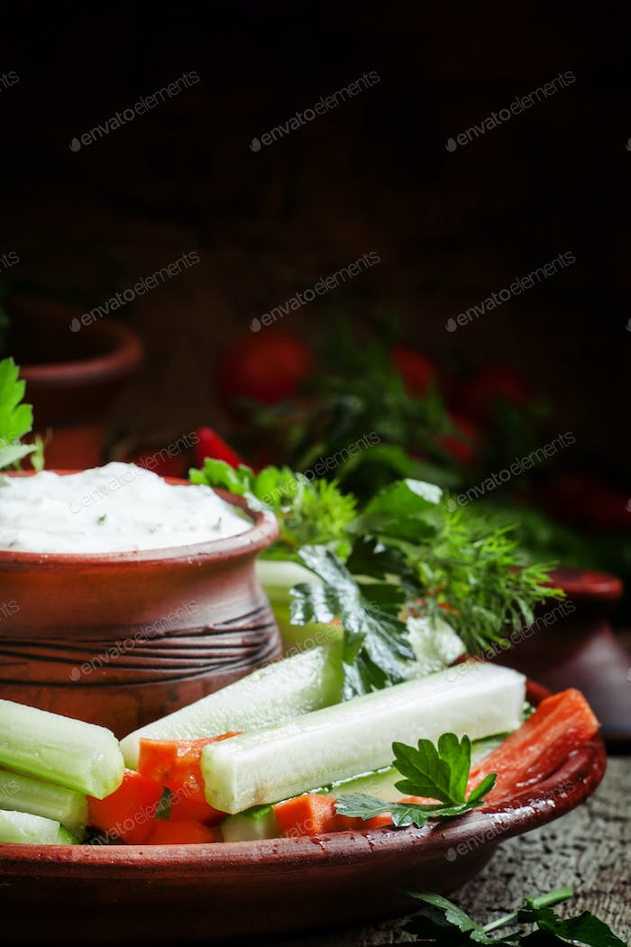 Healthy snacks: cucumber sticks, celery and carrots with ranch dressing