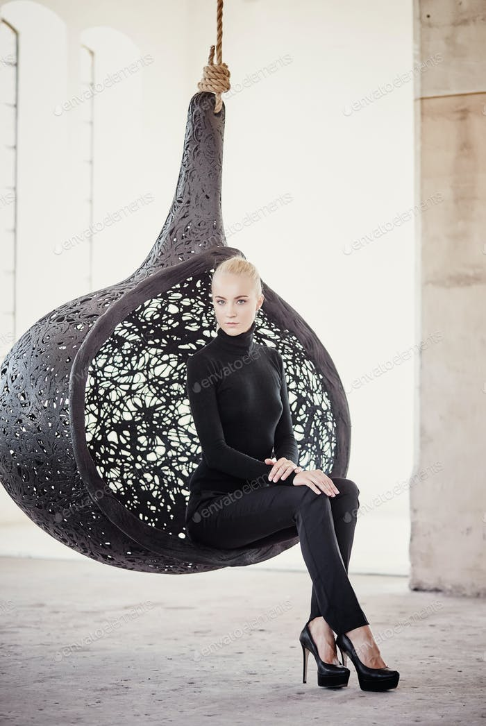 Fashionable blond woman sits on a round chair.
